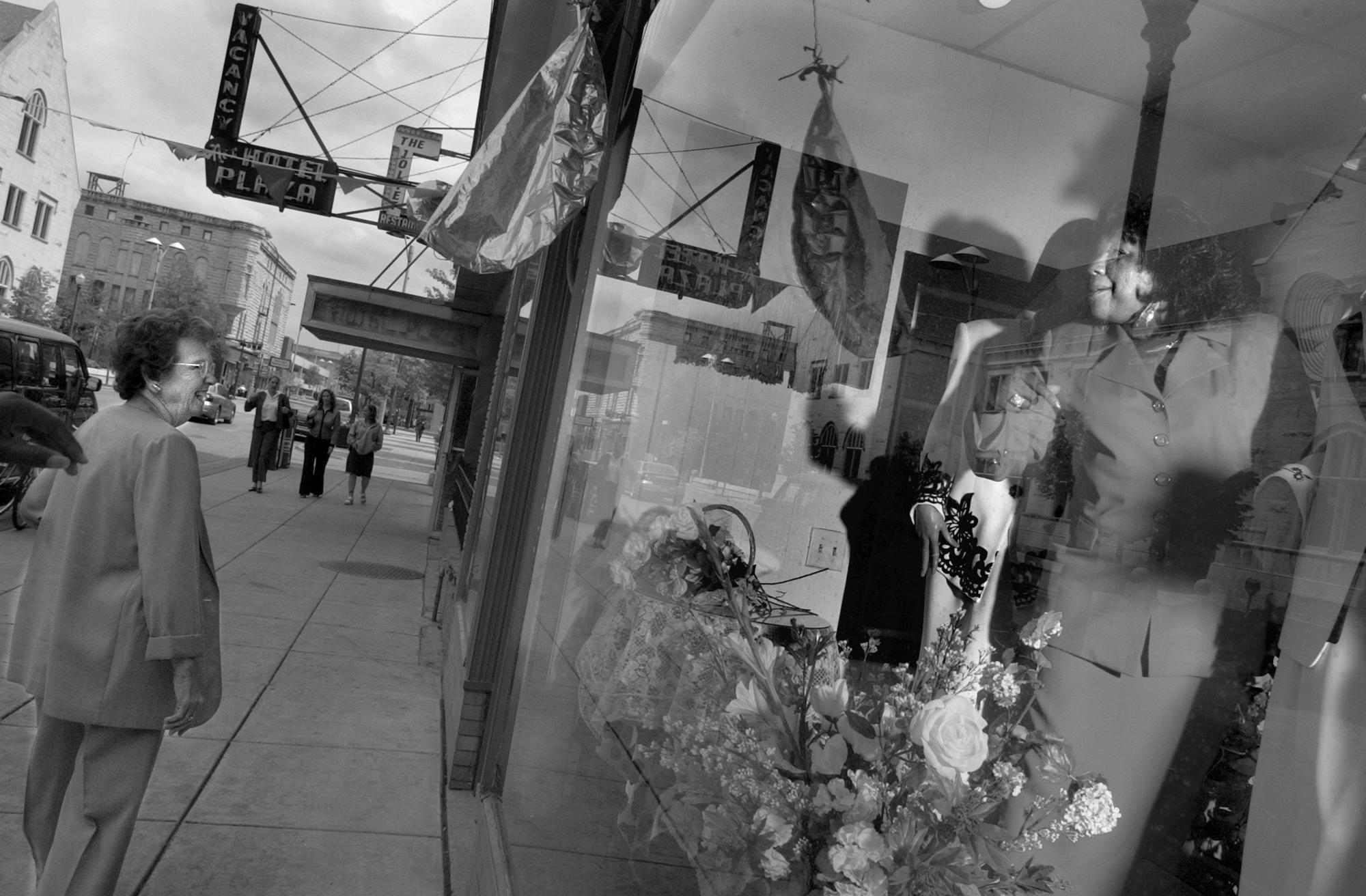 ROBERT SUMNER . HERALD NEWS STAFF PHOTOGRAPHER Elsie Yates waves to a pedestrian who passes her shop, Jole Fashion Boutique, on West Clinton Street in Joliet. She says people often compliment her on the display windows at the store. 082204