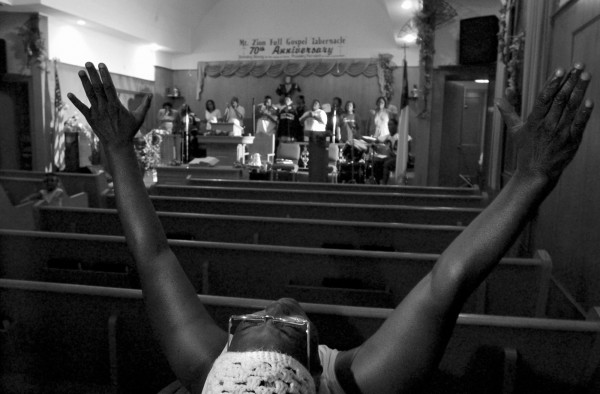 ROBERT SUMNER / HERALD NEWS STAFF PHOTOGRAPHER A patron at Mt. Zion Full Gospel Tabernacle sits in the back of the small church and prays with the choir as they finish their rehearsal. 092304